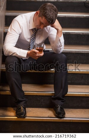 Handsome young man sitting on stairs. portrait of guy drinking whisky and thinking - stock photo