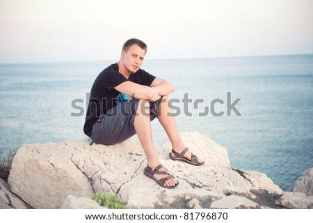 handsome young man sitting on the cliff