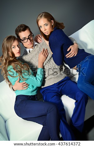 Handsome young man sitting on the couch with two attractive girls. Beauty, fashion.