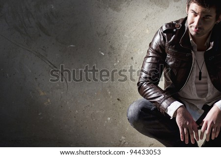 Handsome young man, sitting on the floor - stock photo