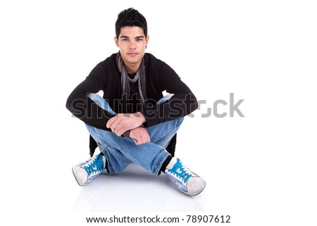 Handsome young man, sitting on the floor, relaxed and confident. Studio shot over white background. - stock photo
