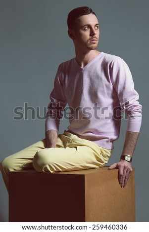 Handsome young man sitting on the nightstand with a thoughtful view - stock photo