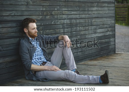 Handsome young man sitting on the wooden floor - stock photo