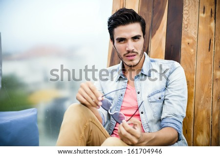 Handsome young man sitting outdoors, looking at the camera with a serious expression - stock photo