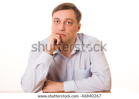 handsome young man sitting pensively on a white background - stock photo