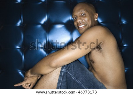Handsome young man sitting shirtless and smiling against a blue padded background. He is pointing towards the ground with one finger. Horizontal shot. - stock photo