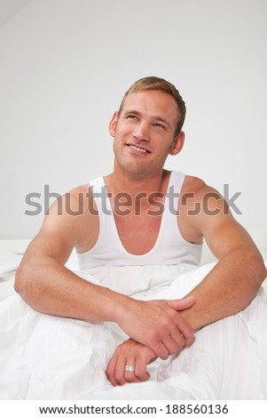 Handsome young man sitting thinking in bed in a white t-shirt staring up into the air with a contemplative expression - stock photo