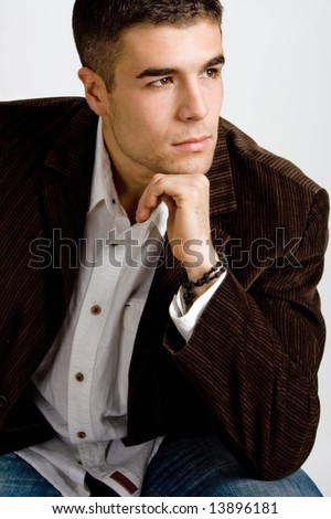 handsome young man sitting with hand under his chin - stock photo