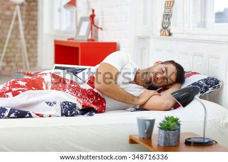 Handsome young man sleeping in bed at home. - stock photo