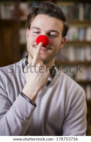 Handsome young man smiling and touching red clown nose, standing in a living room - stock photo
