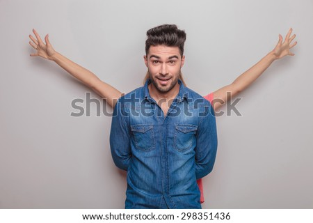 Handsome young man smiling at the camera while his lover is holding her hands up behind him. - stock photo