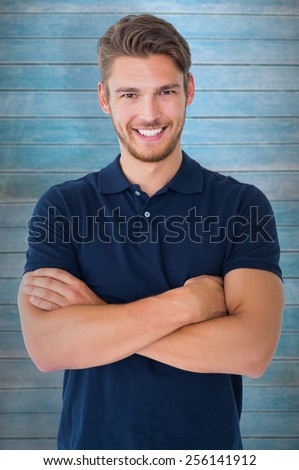 Handsome young man smiling with arms crossed against wooden planks - stock photo