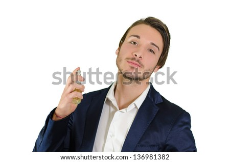 Handsome young man spraying perfume, using fragrance or cologne - stock photo