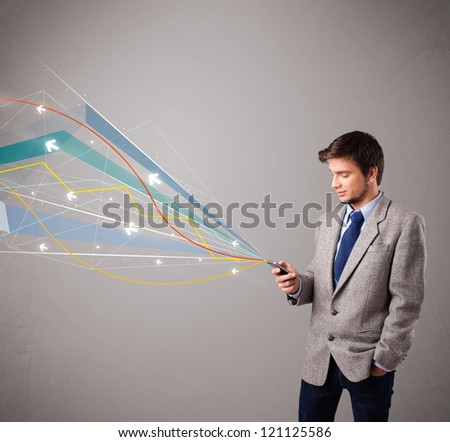 handsome young man standing and holding a phone with colorful abstract arrows and lines - stock photo