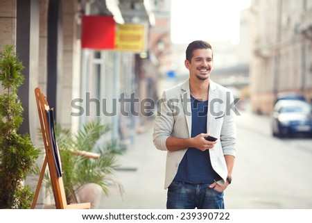 Handsome young man standing on the street holding mobile phone - stock photo