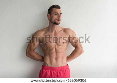 Handsome Young Man Standing Strong Flexing Muscles - Muscular Athletic Bodybuilder Fitness Model Posing After Exercises