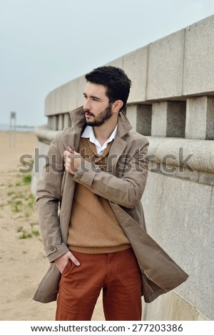 Handsome young man stands in a coat on the sand in windy weather - stock photo