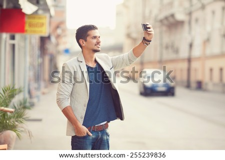 Handsome young man taking a self portrait while walking through the city - stock photo