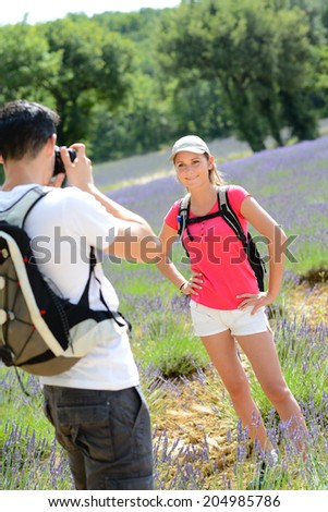 handsome young man taking picture of pretty girlfriend in countryside while trekking during summer vacation - stock photo