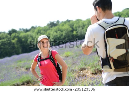 handsome young man taking picture of pretty girlfriend in countryside while trekking in summer vacation - stock photo