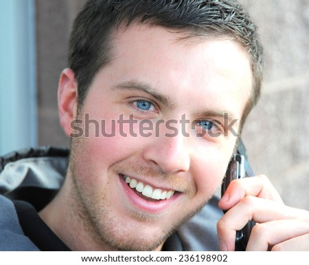 Handsome young man talking on his cellphone outside. - stock photo