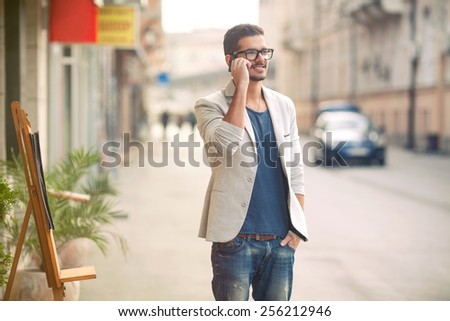 Handsome young man talking on the phone while taking a walk through the city - stock photo
