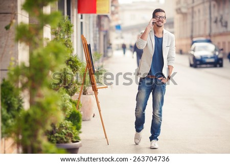 Handsome young man talking on the phone while walking on the street - stock photo