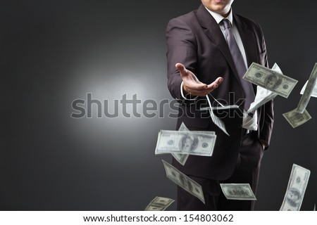 Handsome young man throwing money over dark background - stock photo