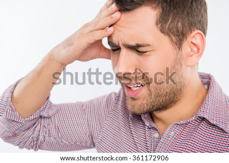 Handsome young man touching his head with one hand feeling strong headache, close up photo - stock photo