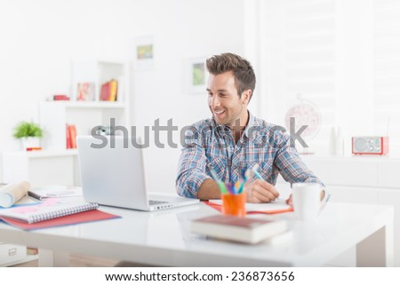 Handsome young man using a laptop in a modern office - stock photo