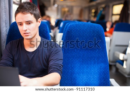 Handsome young man using his laptop computer while on the train (shallow DOF; color toned image) - stock photo