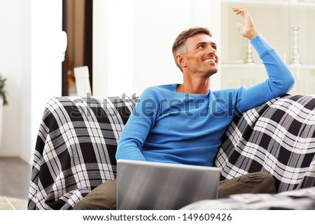 Handsome young man using laptop at home, sitting in armchair, smiling. - stock photo