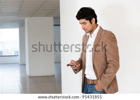 handsome young man using mobile phone with copy space, man reading or sending sms