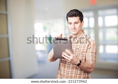 Handsome young man using tablet computer at office or school  - stock photo
