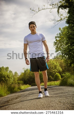 Handsome young man walking and trekking on road in the country in a sunny day, wearing white shirt and baseball cap - stock photo