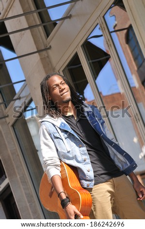 handsome young man walking in the city with a guitar - stock photo