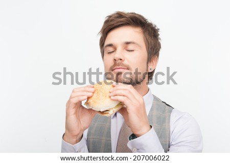 Handsome young man wanted to taste his delicious cheeseburger very much. Isolated on white background - stock photo