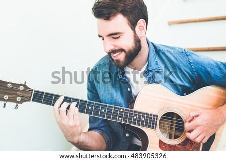 Handsome young man wearing a jeans shirt playing classical guitar. Music, instrument education, entertainment, pop rock star, music concert and learning concept