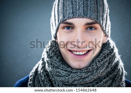 Handsome young man wearing a knit hat and a scarf.