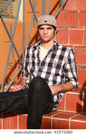 Handsome young man wearing baseball cap outdoors in urban setting. - stock photo