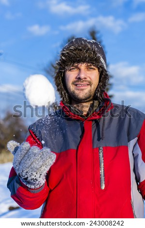 Handsome young man wearing cap and gloves playing with snowballs in a sunny winter day - stock photo