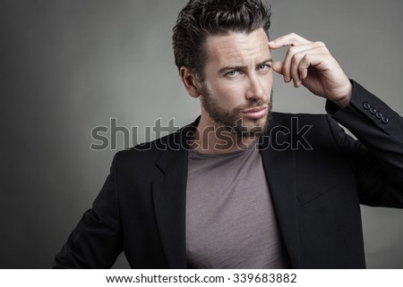 Handsome young man wearing grey suit thinking. He is looking at camera against grey background.