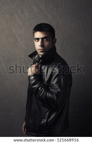 handsome young man wearing leather jacket on grunge background