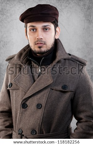 handsome young man wearing overcoat and standing against grey wall