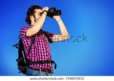 Handsome young man with a backpack looking into the distance with binoculars against blue sky. Active lifestyle, adventure, tourism.  - stock photo