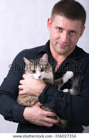 handsome young man with a cat in his arms isolated on white