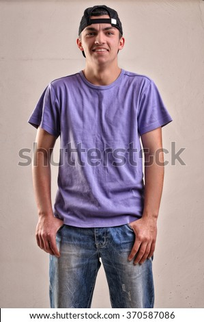 Handsome young man with backwards cap on his head posing in studio - stock photo