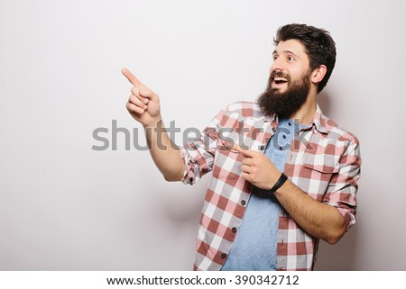 Handsome young man with beard demonstrate  invisible product presentation or advertising  pointed with hands while standing against white background - stock photo