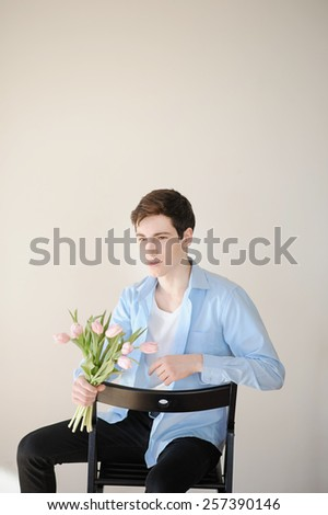 Handsome young man with bouquet of pink tulips - stock photo