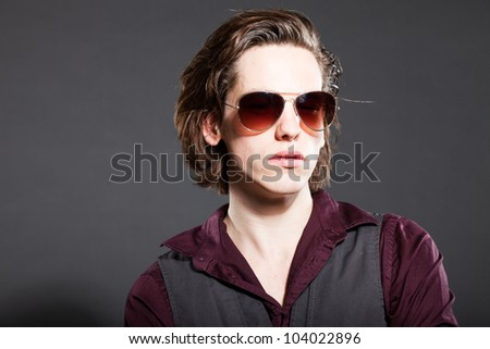 Handsome young man with brown long hair isolated on grey background. Wearing sunglasses. Fashion studio shot. Expressive face.